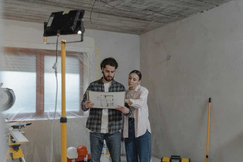 A man and a woman looking at a long-distance house remodelling plan