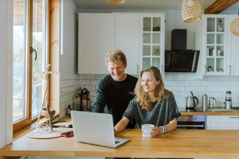 A man and a woman looking at their laptop, preparing for a video call